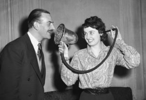 25th March 1958:  Angela Sinclair demonstrating a Chase silver ear trumpet, made in 1880 and used by Queen Victoria, at the 'Escape From Deafness' exhibition in Park Lane House, Park Lane, London.  (Photo by Ron Case/Keystone/Getty Images)